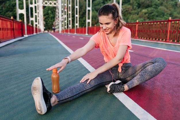 Zainspirowana biała młoda kobieta rozciągająca się z uśmiechem. portret pięknej dziewczyny w stroje sportowe przygotowuje się do maratonu na torze żużlowym.
