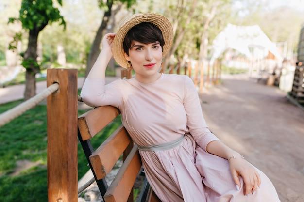 Zainspirowana brązowowłosa dziewczyna odpoczywa na drewnianej ławce, czekając, aż przyjaciele spędzą razem czas na świeżym powietrzu