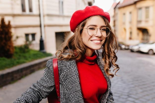 Zainspirowana brązowowłosa dziewczyna z radosną miną przechadza się po ulicy w ciepły dzień
