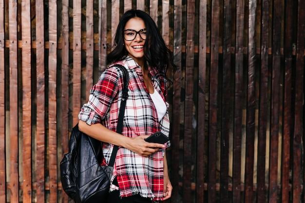 Zainspirowana brunetka dziewczyna z telefonem, pozowanie na drewnianej ścianie z wesołym uśmiechem. plenerowy portret fascynującej latynoski w stylowych okularach.
