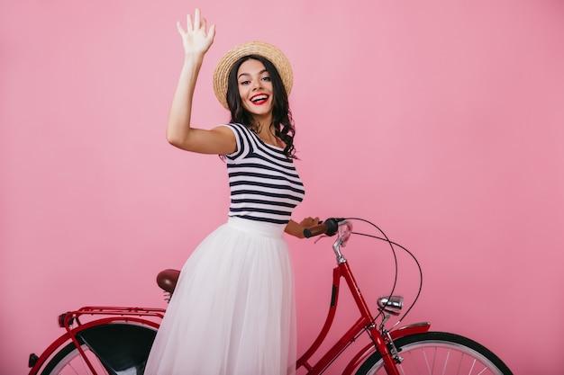 Zainspirowana brunetka kobieta w podkoszulku w paski z czerwonym rowerem. blitnie opalona dama stojąca z uśmiechem.