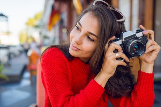Zainspirowana brunetka, która dobrze się bawi i robi zdjęcia podczas wakacji. zimny sezon. ubrana w stylowy czerwony sweter z dzianiny.