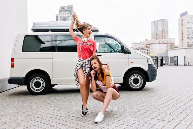 Zainspirowana brunetka w żółtej koszuli siedzi ze skrzyżowanymi nogami obok białego samochodu, podczas gdy jej przyjaciółka bawi się długimi włosami