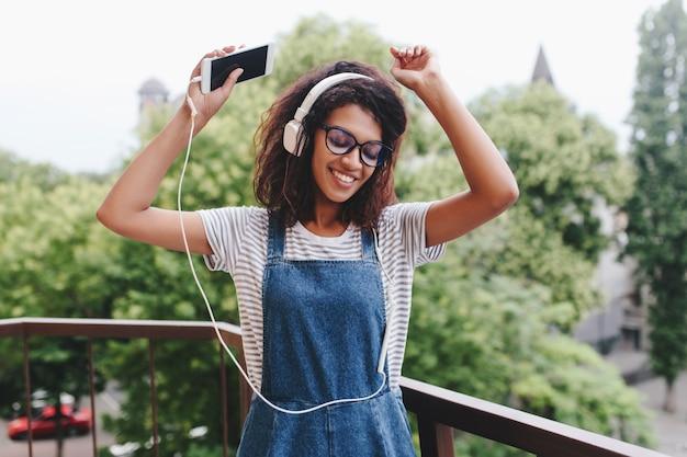Zainspirowana czarna dziewczyna z modną kręconą fryzurą tańczy na balkonie z drzewami