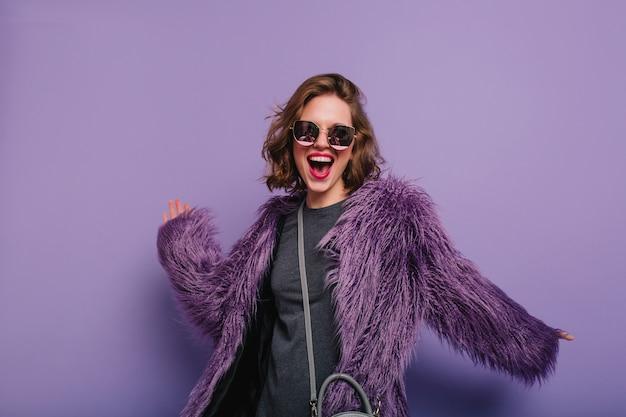 Zainspirowana dama ze stylowym makijażem tańczy w fioletowym futrze i się śmieje