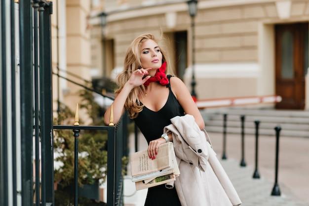 Zainspirowana dziewczyna o długich blond włosach odwracająca wzrok i delikatnie dotykająca palcami twarzy, stojąca na ulicy