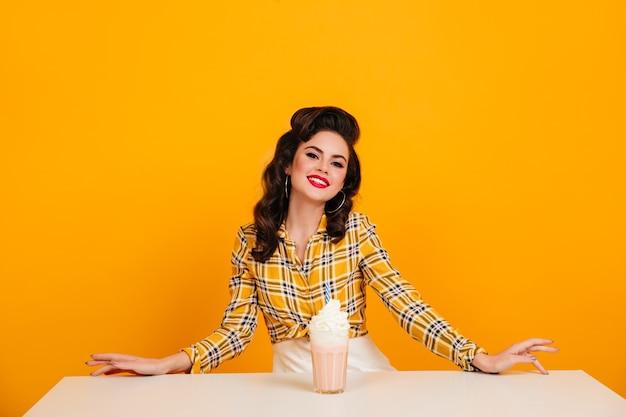Zainspirowana dziewczyna pinup z kieliszkiem koktajlu. strzał studio zgrabny brunetka kobieta z koktajlem mlecznym.