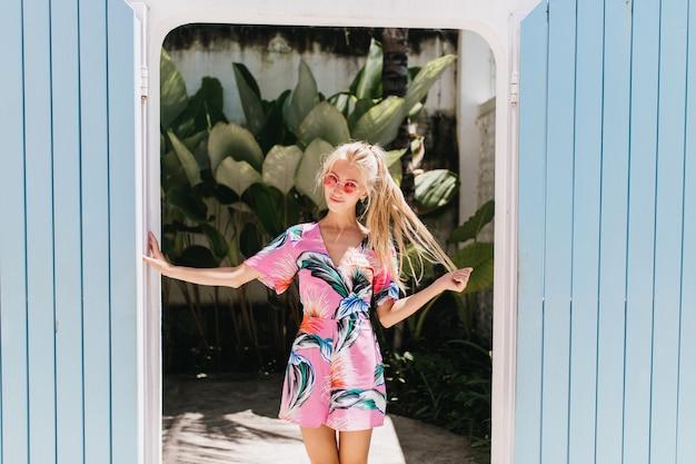 Zainspirowana dziewczyna stojąca w pewnej pozie i bawiąca się długimi blond włosami.
