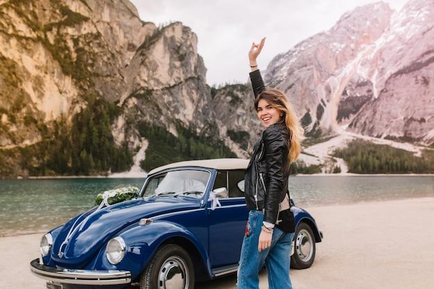 Zainspirowana dziewczyna w czarnej skórzanej kurtce bawiąca się na świeżym powietrzu podczas wizyty w górskim jeziorze