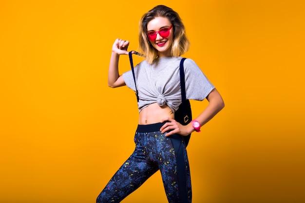 Zainspirowana dziewczyna w czerwonych okularach przeciwsłonecznych z krótką fryzurą, trzymając butelkę wody i uśmiechnięta. kryty portret śmiejąc się europejskiej modelki na białym tle na żółtym tle.