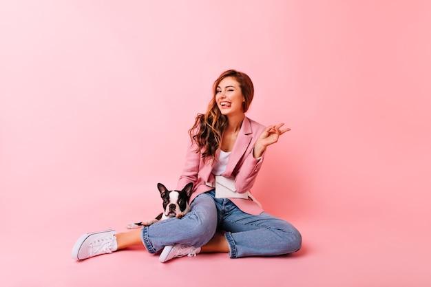 Zainspirowana dziewczyna w dżinsach i gumowych butach pozuje z buldogiem. kryty portret entuzjastycznej imbirowej modelki siedzącej na podłodze z szczeniakiem.