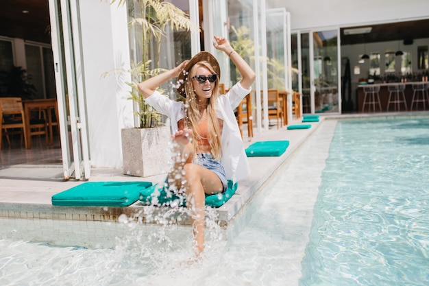 Zainspirowana dziewczyna w eleganckim letnim kapeluszu bawi się wodą i śmiejąc się. zadowolony europejska blondynka chłodzenie w basenie.