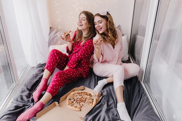 Zainspirowana dziewczyna w różowych skarpetkach jedząca pizzę z najlepszą przyjaciółką. wewnątrz zdjęcie dwóch sióstr w piżamie delektujących się włoskim jedzeniem w łóżku.