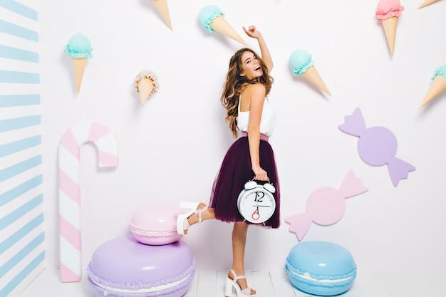 Zainspirowana dziewczyna w stylowych butach na wysokim obcasie, zabawy na imprezie tematycznej i śmiechu. kryty portret śmiesznej młodej kobiety z modną fryzurą, trzymając duży zegar i pozuje w pokoju ozdobionym słodyczami.