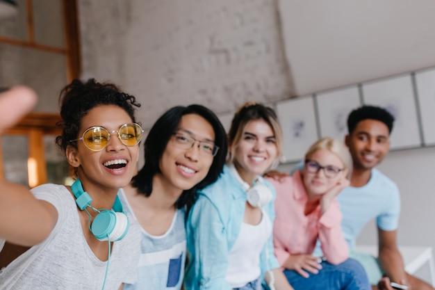 Zainspirowana dziewczyna w stylowych żółtych okularach robi selfie z kolegą z azjatyckiego uniwersytetu i innymi studentami. urocza młoda kobieta o jasnobrązowej skórze, fotografująca się z ludźmi.