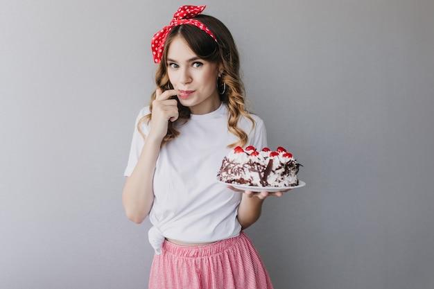 Zainspirowana dziewczyna z falowanymi włosami degustująca tort urodzinowy. czarująca modelka ze stawianiem ciasto.