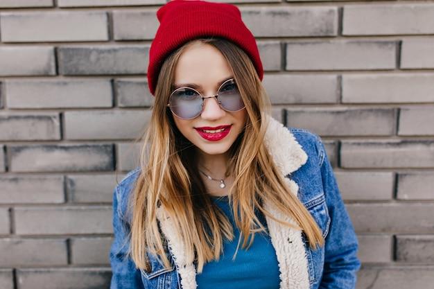 Zainspirowana dziewczynka kaukaski z czerwonymi ustami pozuje na świeżym powietrzu z radosnym uśmiechem. wyrafinowana modelka w dżinsowej kurtce relaksująca podczas wiosennego spaceru.