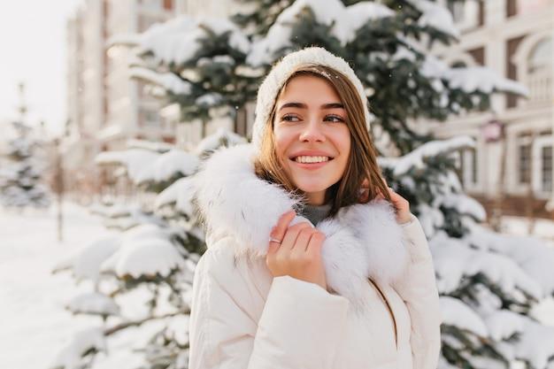 Zainspirowana europejska dama nosi biały strój zimowy, podziwiając widoki natury. odkryty portret pięknej kaukaski modelki uśmiecha się