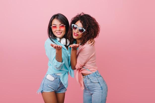Zainspirowana europejska dziewczyna o brązowej skórze wysyła pocałunek z afrykańską młodą kobietą. portret modnej kobiety z kręconymi włosami nosi ciemne okulary przeciwsłoneczne i modne dżinsy.