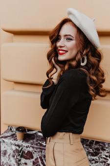 Zainspirowana francuska kobieta z długimi fryzurami pozuje w eleganckim berecie. zewnątrz portret beztroskiej rudej dziewczyny.