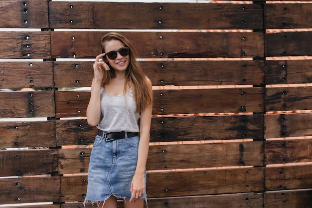 Zainspirowana kaukaska dziewczyna w modnych ubraniach pozuje w pobliżu drewnianej ściany. zdjęcie spektakularnej pani w stylowej dżinsowej spódnicy z uśmiechem