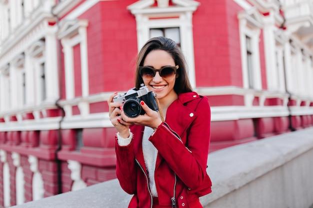Zainspirowana kaukaski dziewczyna pozuje ze szczęśliwym uśmiechem po ulicznej sesji zdjęciowej