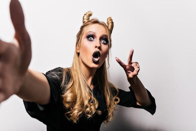 Zainspirowana kaukaski kobieta w stroju czarownicy podejmowania selfie. niesamowita dziewczyna z ciemnym makijażem przygotowuje się do halloweenowej imprezy.