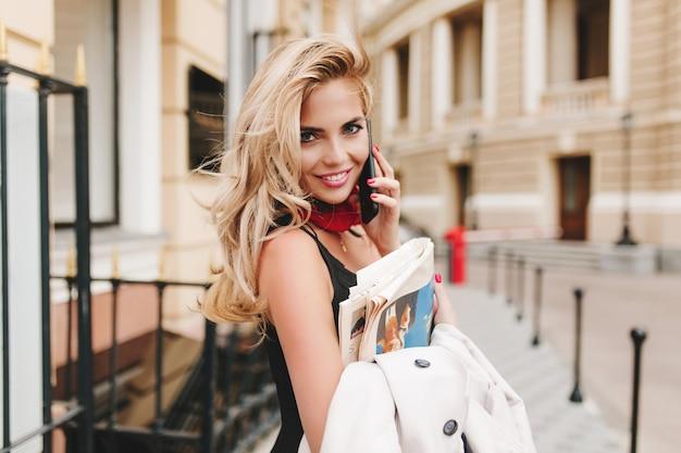 Zainspirowana kobieta kręcone trzymając kurtkę śmiejąc się podczas rozmowy z kimś przez telefon