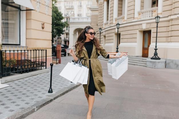 Zainspirowana kobieta o długich kręconych włosach idąca ulicą po zakupach i rozglądaniu się