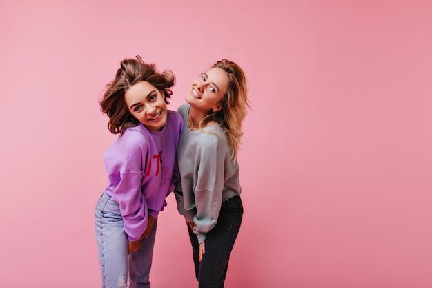 Zainspirowana kobieta w fioletowej koszuli bawi się z najlepszym przyjacielem. wewnątrz portret dwóch niesamowitych pań w swobodnym stroju.