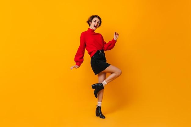 Zainspirowana kobieta w krótkiej spódniczce tańczy na żółtej ścianie