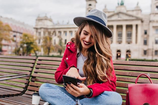 Zainspirowana kobieta z jasnym makijażem, siedząca z założonymi nogami na ulicy i wysyłająca sms-a