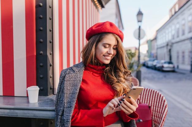 Zainspirowana kobieta z wyrazem zadowolenia, wysyłając sms-a podczas picia kawy w pobliżu kawiarni na świeżym powietrzu