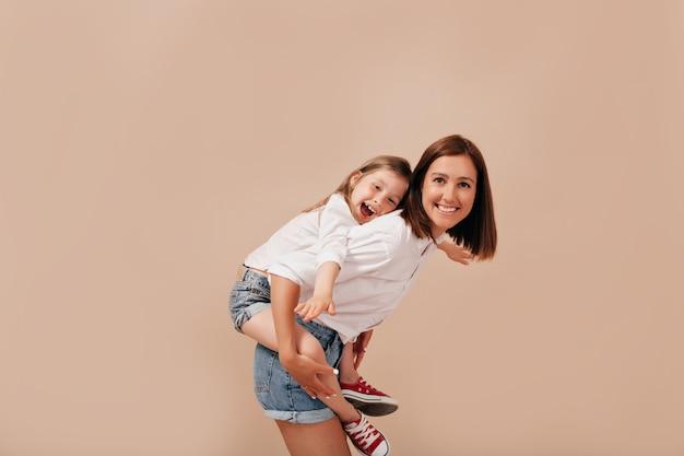 Zainspirowana młoda kobieta bez makijażu, spędzająca czas z córką, niosąca na barana na odosobnionym tle.