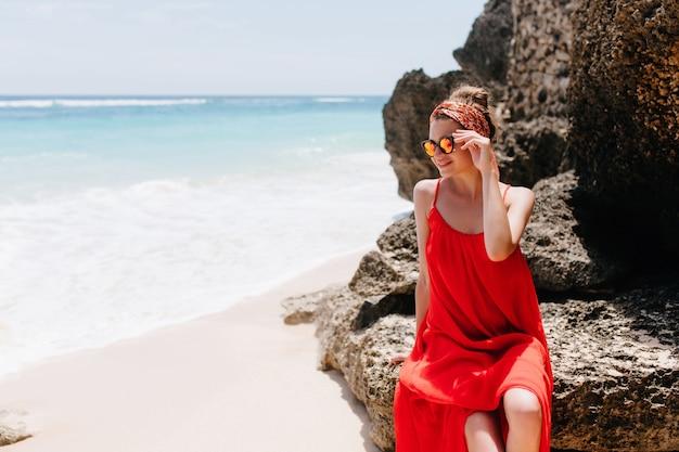 Zainspirowana młoda kobieta siedzi na skale i patrząc na ocean. niesamowita kaukaska modelka dotykająca okularów przeciwsłonecznych, podziwiając widoki na niebo na dzikiej plaży.