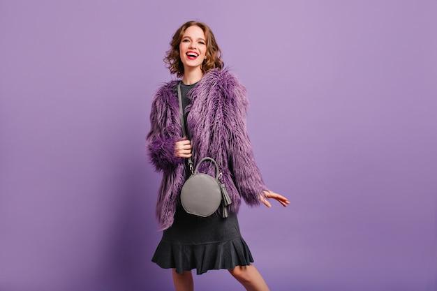 Zainspirowana modelka w ślicznej szarej torebce, patrząc na kamery z uśmiechem