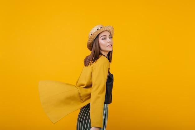 Zainspirowana pani w żółtej kurtce pozuje. wewnątrz zdjęcie beztroskiej modelki w słomkowym kapeluszu.