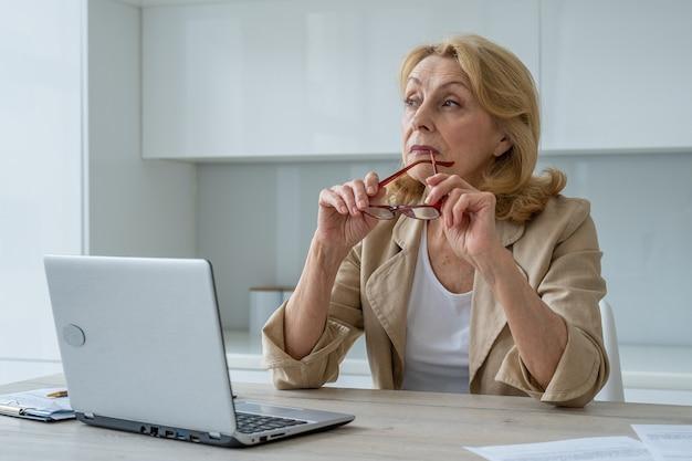 Zainspirowana starsza bizneswoman rozważa nowe kreatywne pomysły w miejscu pracy