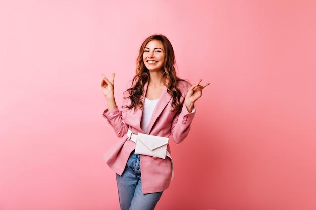 Zainspirowana szczupła dziewczyna dobrze się bawi. niesamowita kaukaska dama w różowej kurtce uśmiechnięta