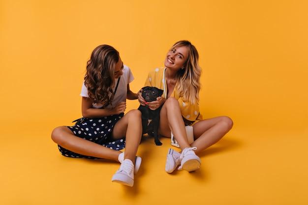 Zainspirowane koleżanki siedzą na podłodze i bawią się z buldogiem francuskim. wewnątrz portret wesołych dziewczyn odpoczywających podczas sesji portretowej z psem.