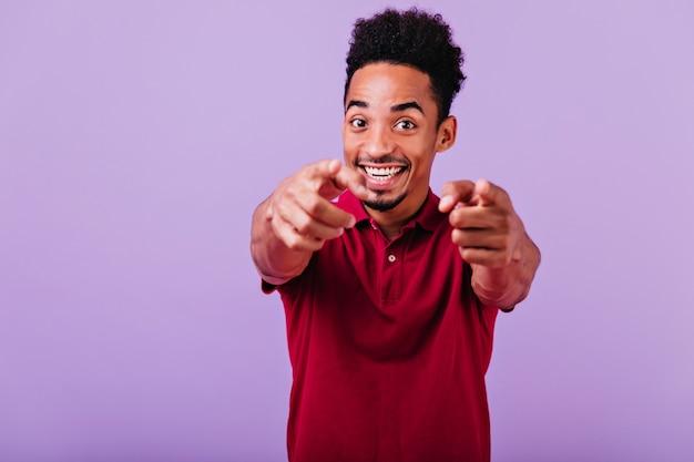 Zainspirowany afrykański facet palcem wskazującym. śmiejąc się pozytywny czarny człowiek uśmiecha się.