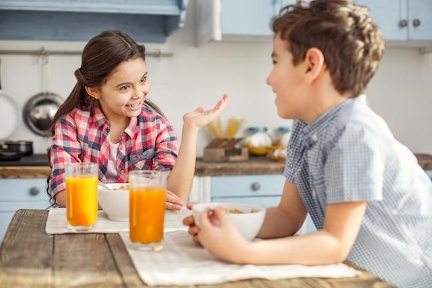 Zainspirowany. całkiem szczęśliwa mała ciemnowłosa dziewczyna uśmiecha się i rozmawia z bratem podczas ich śniadania