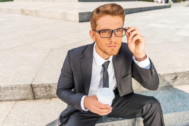 Zainspirowany filiżanką świeżej kawy. widok z góry na rozważny młody człowiek w formalwear, trzymający filiżankę kawy i dopasowujący okulary, siedząc na zewnątrz