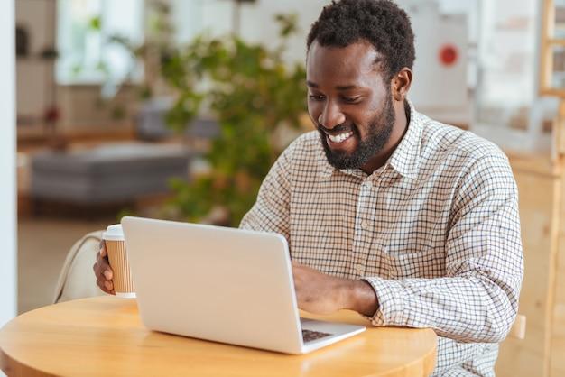 Zainspirowany informatyk. uroczy wesoły mężczyzna siedzi przy stoliku w kawiarni i opracowuje nową aplikację na swoim laptopie, trzymając filiżankę kawy