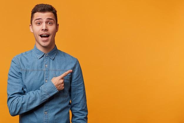 Zainspirowany młody człowiek w dżinsowej koszuli prosi o zwrócenie uwagi na coś bardzo interesującego