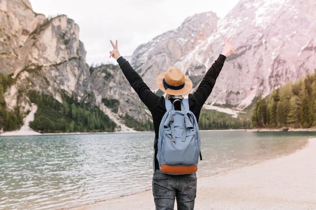 Zainspirowany podróżnik w jasnobrązowym kapeluszu cieszący się wolnością po ucieczce z miasta i spędzaniu czasu z naturą