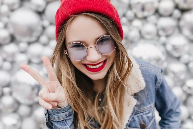 Zainteresowana biała dziewczyna z wesołym uśmiechem pozuje ze znakiem pokoju. zbliżenie atrakcyjnej pani w dżinsowej kurtce wygłupów podczas sesji zdjęciowej na błyszczącej ścianie.