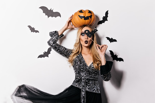 Zainteresowana długowłosa dziewczyna trzymająca pomarańczową dynię podczas sesji zdjęciowej na halloween. wewnątrz zdjęcie atrakcyjnej blondynki w stroju wiedźmy.