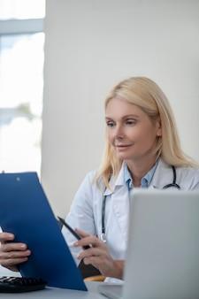 Zainteresowana długowłosą kobietą lekarz z teczką i piórem czytającym dokument w biurze w godzinach popołudniowych