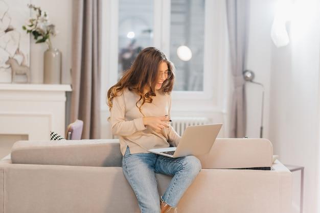 Zainteresowana dziewczyna kręcone za pomocą laptopa, siedząc na kanapie i śmiejąc się